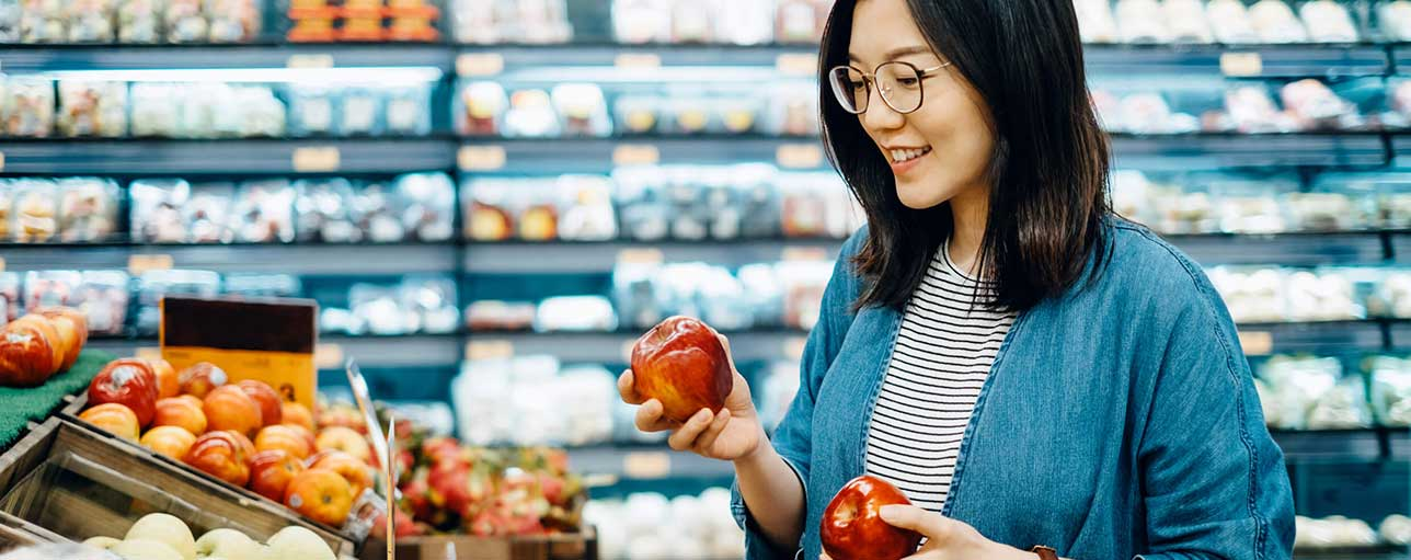 d5f455b1 Woman picking apples in grocery store